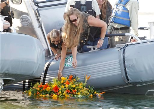 Tiffany Hartley, left, and family members, lay a wreath near the site where her husband, David Hartley, was shot last month on Falcon Lake in Zapata, Texas. (AP Photo/Eric Gay, File)