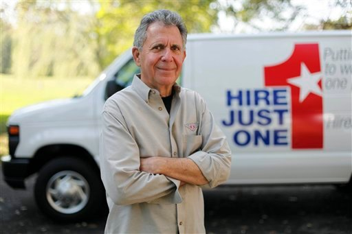 Philanthropist Gene Epstein poses in front of a van advertising his Hire Just One initiative, in Newtown, Pa. (AP)