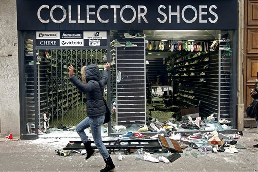 A woman runs past a devastated shoe shop during clashes in Lyon, central France, Tuesday, Oct. 19, 2010. (AP Photo/Laurent Cipriani)