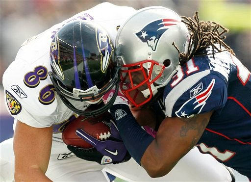 In this photo made Oct. 17, 2010, Baltimore Ravens tight end Todd Heap, left, takes a hit from New England Patriots safety Brandon Meriweather, right, during an NFL football game at Gillette Stadium in Foxborough, Mass.