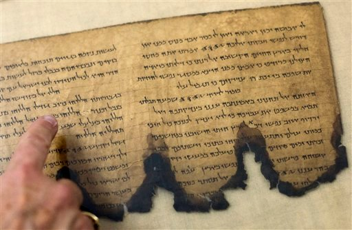 A worker of the IAA, Israel Antiquities Authority, points at a fragment of the Dead Sea Scrolls in a laboratory in Jerusalem, Tuesday, Oct. 19, 2010.