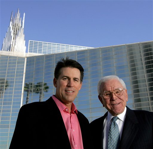 This Feb. 9, 2006 file photo shows Robert A. Schuller, left, poses for a photo with his father, Robert H. Schuller, outside the Crystal Cathedral in Orange, Calif. (AP Photo/Chris Carlson, File)
