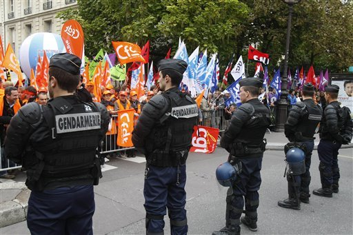 French riot policemen face demonstrators protesting against government retirement reforms in front of the Senate building in Paris, Tuesday Oct. 5, 2010. (AP Photo/Remy de la Mauviniere)