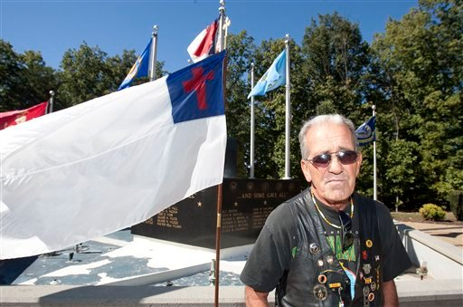 In a Saturday Oct. 16, 2010 photo, Ray Martini, an Air Force Veteran, stands beside a Christian flag flying in front of the Veterans Memorial at Central Park in King, N.C.