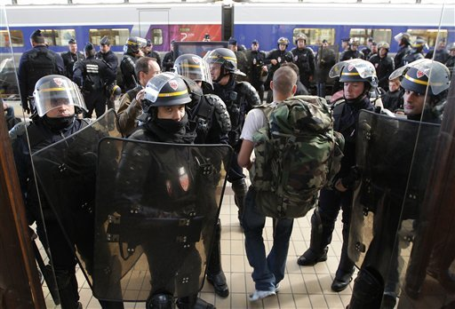 French riot police officers secure the area at the Bordeaux train station, southwestern France, as a passenger arrive during a demonstration against President Nicolas Sarkozy's bid to raise the retirement age to 62. (AP Photo/Bob Edme)
