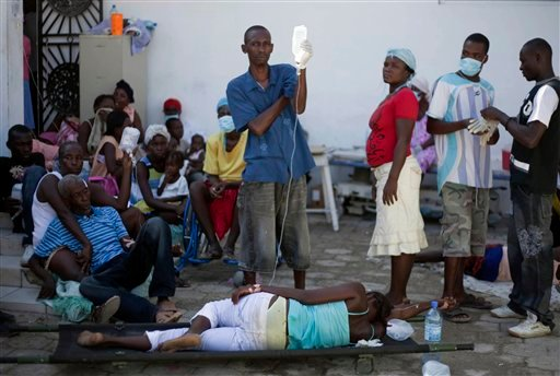 Patients suffering from diarrhea and other cholera symptoms are helped by other residents as they wait for treatment at the St. Nicholas hospital in Saint Marc, Haiti, Friday, Oct. 22, 2010.