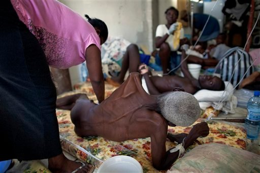 A man, suffering from diarrhea and other cholera symptoms, is cleaned by a woman as he lies next to other sick people.