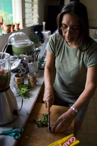 In this Saturday, Oct. 16, 2010 photo, Lillie Gonzales chops up vegetables from her home garden, in Omao, Hawaii on the island of Kauai.