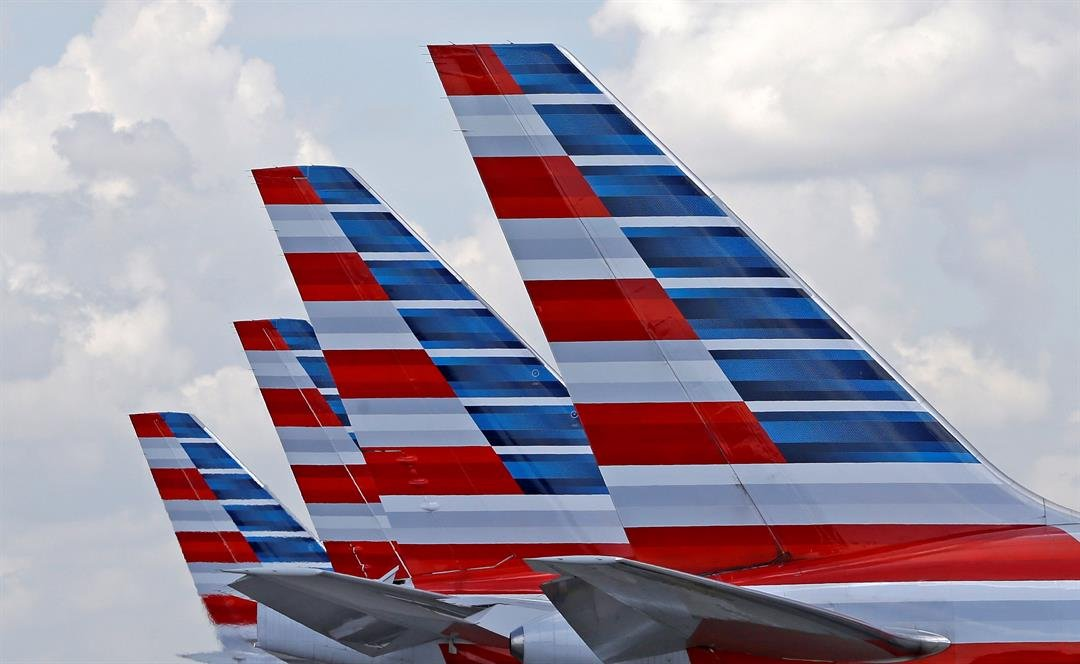 FILE - This July 17, 2015, file photo shows the tails of four American Airlines passenger planes parked at Miami International Airport, in Miami.  (AP Photo/Alan Diaz, File)