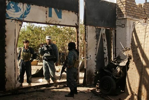 Afghan security forces secure an entrance next to the wreckage of a suicide bomber's vehicle at a UN compound in Herat, west of Kabul, Afghanistan, Saturday, Oct. 23, 2010. (AP Photo/Reza Shirmohammadi)