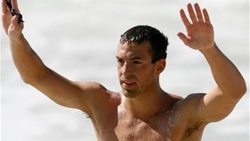 Fran Crippen of the U.S. waves after finishing first and winning the gold medal in the Pan Am erican Games 10 km men's swimming marathon at Copacabana beach in Rio de Janeiro. (AP Photo/Dario Lopez-Mills, File).