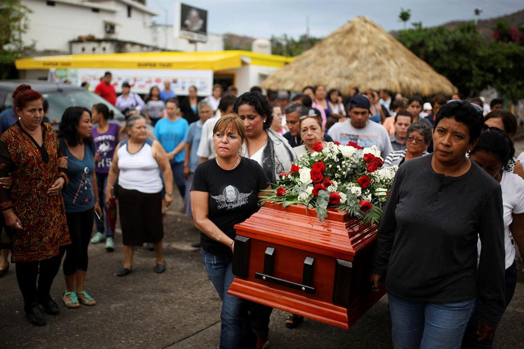 In this March 8, 2017 photo, members of the Solecito search group carry the coffin of Pedro Huesca, a police detective who disappeared in 2013 and was recently found in a mass grave, as they walk to the cemetery in Palmas de Abajo, Veracruz, Mexico.
