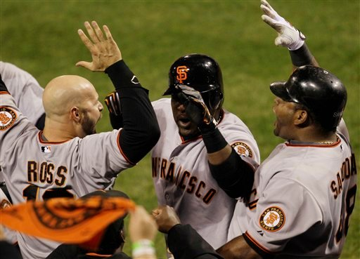 San Francisco Giants' Cody Ross (13) and Pablo Sandoval (48) congratulate Juan Uribe after Uribe hit a home run during the eighth inning.