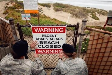 Airmen 1st class Daniel Clark, left, and Staff Sgt. Keri Embry, post a sign warning surfers of a recent shark attack Friday, Oct. 22, 2010, at Vandenburg Air Force Base, Calif.
