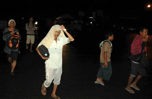 In this Monday, Oct. 25, 2010 photo, residents flee their homes to higher ground after a strong earthquake is felt in Padang, West Sumatra, Indonesia. (AP Photo)