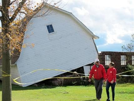 Two Red Cross workers walk away from a barn that was lifted off its foundation by a tornado Tuesday, Oct. 26, 2010, in Mount Pleasant, Wis. Wisconsin is one of eleven states in the midwest under a high wind warning. (AP Photo/Carrie Antlfinger)