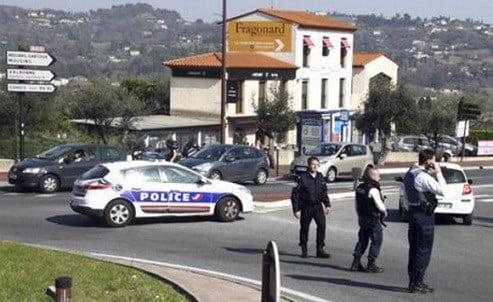 A police car blocks a road after an attack in a high school in Grasse, southern France, Thursday, March 16, 2017.
