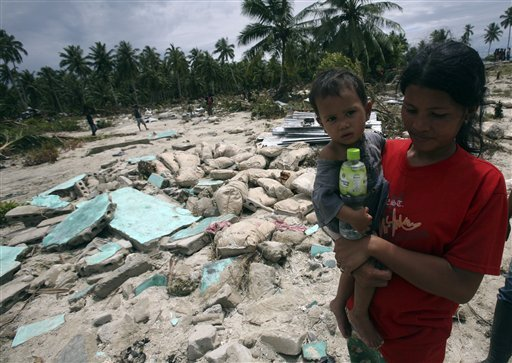 Tsunami survivors make their way past damaged houses after their village was hit by Monday's earthquake-triggered tsunami at Parorogat village, Pagai island, West Sumatra, Indonesia, on Thursday, Oct. 28, 2010. (AP Photo/Achmad Ibrahim)