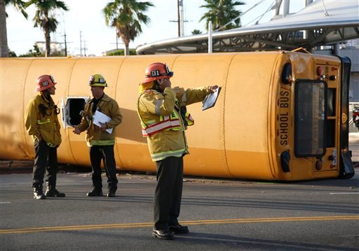 os Angeles City firefighters investigate the scene of an accident involving a school bus and another vehicle at the intersection of First and Soto Streets in the Boyle Heights area of Los Angeles on Monday, Oct. 25, 2010.