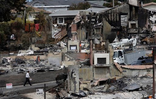 In this Sept. 13, 2010, file photo a man walks past the remains of homes damaged from a fire caused by a pipeline explosion in a mostly residential area in San Bruno, Calif.