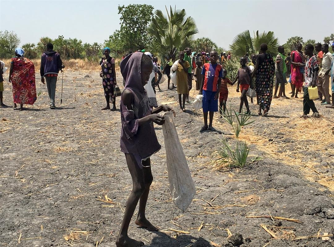 In this photo taken Wednesday, March 1, 2017, Lulu Yurdio, 12, collects food aid for himself and his two siblings and parents who remain hiding in the bush, in Padeah, South Sudan. (AP Photo/Sam Mednick)