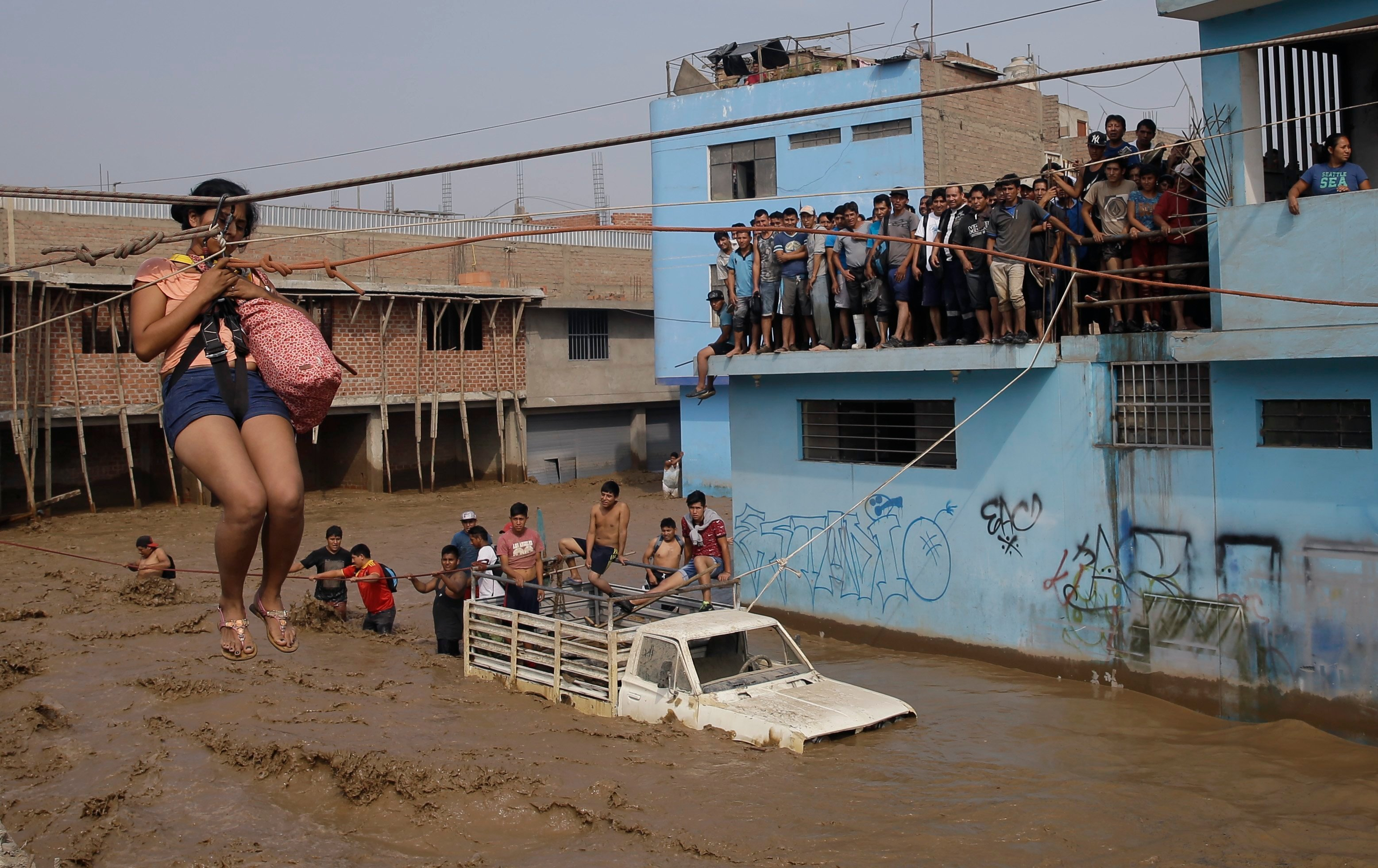 A woman is pulled to safety in a zipline harness in Lima, Peru, Friday, March 17, 2017. Intense rains and mudslides over the past three days have wrought havoc around the Andean nation and caught residents in Lima, a desert city of 10 million where it alm