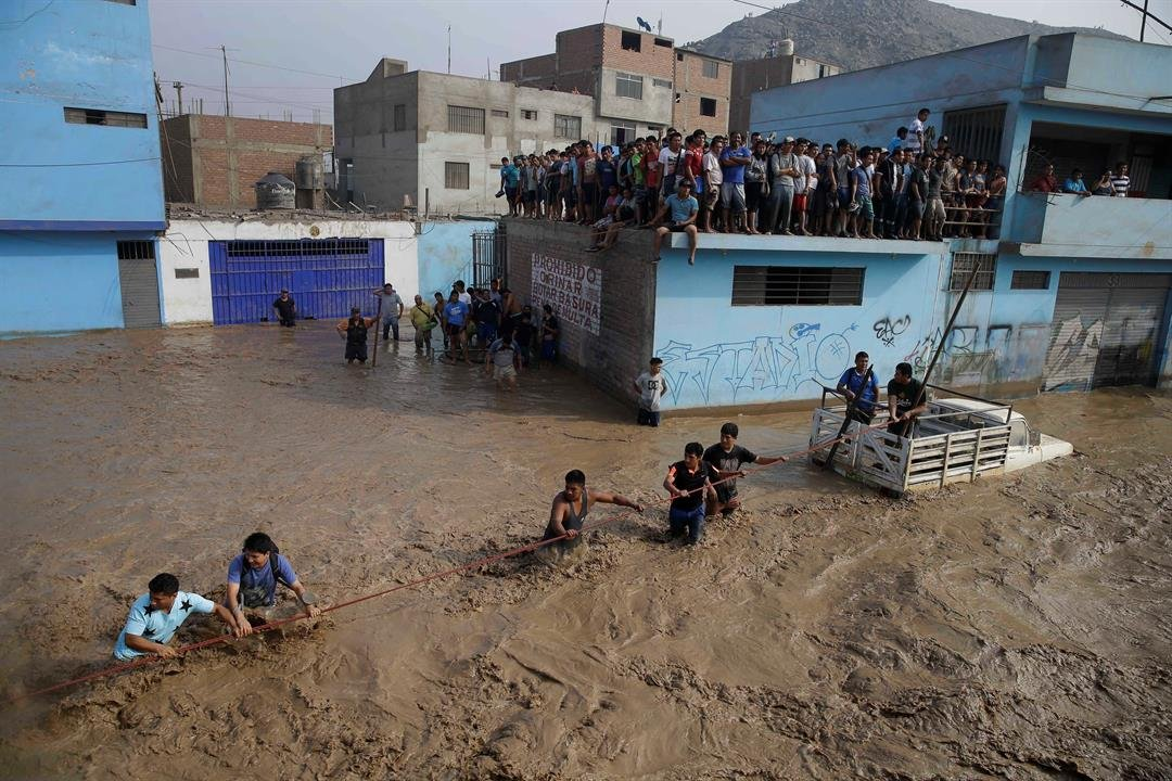 Men hold onto a rope as they wade through flood waters towards safety in Lima, Peru, Friday, March 17, 2017. Intense rains and mudslides over the past three days have wrought havoc around the Andean nation and caught residents in Lima, a desert city of 10