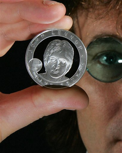 In this image dated Oct. 18, 2010, released by the British Royal Mint, showing John Lennon look-a-like Alan Swoffer, poses with the new John Lennon £5 coin which goes on sale Friday Oct. 29, 2010.