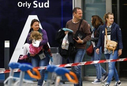Travelers evacuate Orly airport, south of Paris, Saturday, March, 18, 2017.