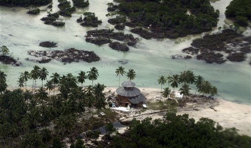 This aerial photo shows a damaged building in a village flattened by Monday's earthquake triggered tsunami on Pagai island, West Sumatra, Indonesia, Wednesday, Oct. 27, 2010.