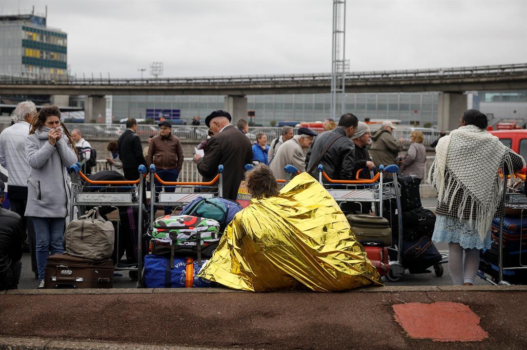 Travelers wait outside Orly airport on Saturday (AP Photo/Kamil Zihnioglu)