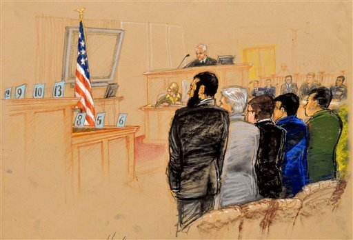 Canadian Omar Khadr, front left, stands with his defense team as his verdict is read at Camp Justice on Guantanamo Bay U.S. Naval Base in Cuba, Sunday Oct. 31, 2010. (AP Photo/Janet Hamlin, Pool)