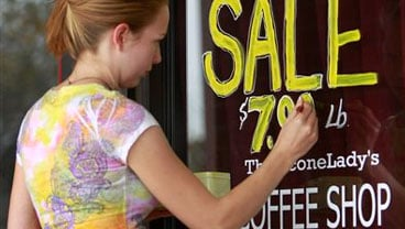 Oct. 25, 2010 photo: Carrie Warden, manager of The Sconelady's Coffee Shop, paints a sign for their fall coffee sale in Lawrence, Kan. Americans slowed their spending in September to the weakest pace in three months.(AP Photo/Orlin Wagner)