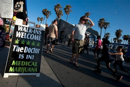 In this photo taken June 20, 2010, a sandwich board welcomes walk-ins to Kush Doctor, a medical marijuana dispensary along the Venice Beach Boardwalk in Los Angeles. (AP Photo/Adam Lau)