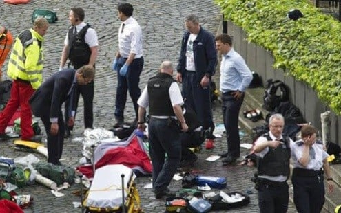 Conservative MP Tobias Ellwood, left, stands amongst the emergency services at the scene outside the Palace of Westminster, London, Wednesday, March 22, 2017.