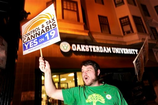 Daniel Costa, a volunteer with the campaign to legalize marijuana, rallies last minute voters to support Proposition 19 shortly before polls closed on Tuesday, Nov. 2, 2010, in Oakland, Calif.