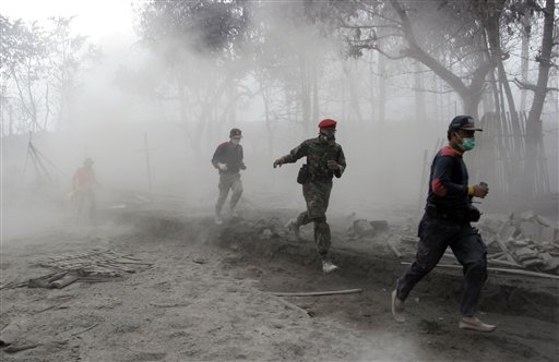 Indonesian soldier and rescuers run after an eruption of Mount Merapi in Argomulyo, Yogyakarta, Indonesia, Friday, Nov. 5, 2010. (AP Photo/Trisnadi)