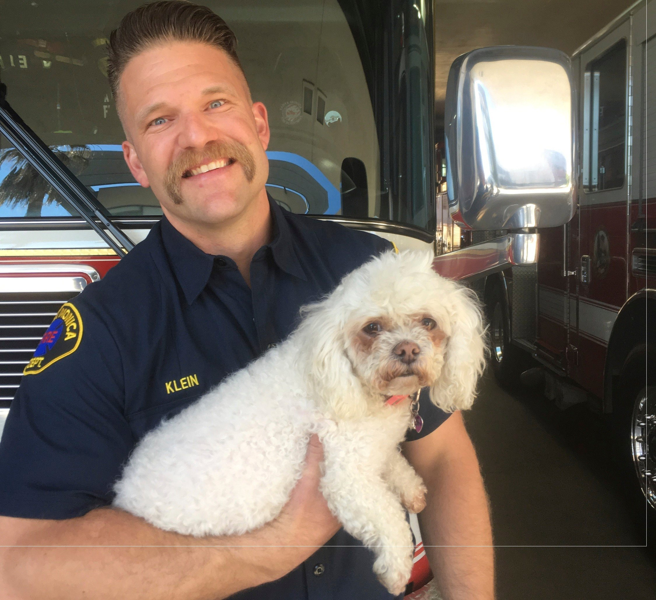 In this photo released by dog owner Crystal Lamirande, Santa Monica Firefighter Andrew Klein holds Nalu in Santa Monica, Calif., on Thursday, March 23, 2017. (Crystal Lamirande via AP)