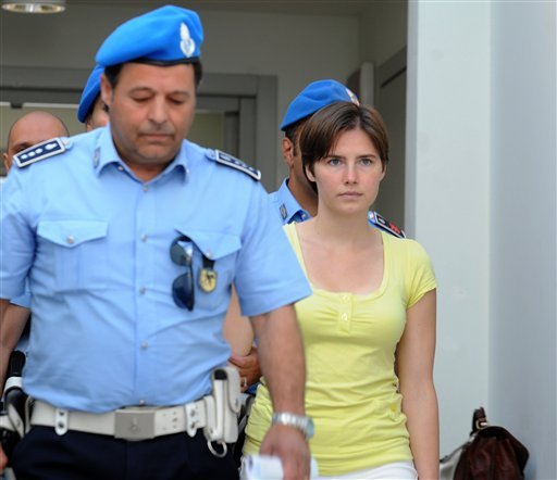 In this June 1, 2010 file photo, jailed US student Amanda Knox, right, is escorted by police as she arrives for a preliminary hearing in Perugia, Italy. (AP Photo/Fabrizio Troccoli, file)