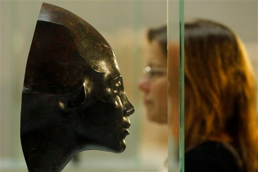 A woman passes the sculpture 'Portrait of Anni Mewes' from 1921 by German artist Edwin Scharff during a press preview of so called 'degenerate' art in Berlin on Monday, Nov. 8, 2010.