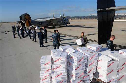 In this Tuesday, Nov. 9, 2010 photo released by the U.S. Navy, sailors from Fleet Logistics Squadron (VRC) 30 load meat, bread and plastic dinnerware into a C-2A Greyhound logistics aircraft at Naval Base Coronado in San Diego, Calif.