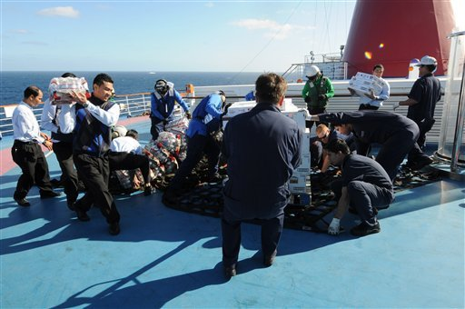 U.S. Navy sailors assigned to the aircraft carrier USS Ronald Reagan (CVN 76) help crew members of the Carnival cruise ship Splendor unload food and water sent from the carrier.