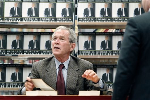 "Former President George W. Bush talks to a book store customer while signing a copy of his book ""Decision Points"" at a store near his Dallas home, Tuesday, Nov. 9, 2010. (AP Photo/LM Otero)"