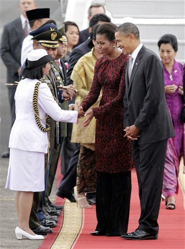 U.S. President Barack Obama, right, smiles as he looks at an Indonesian female officer greeting first lady Michelle as Obama arrives at Halim Perdanakusumah airport in Jakarta, Indonesia, Tuesday, Nov. 9, 2010. (AP Photo/Tatan Syuflana)