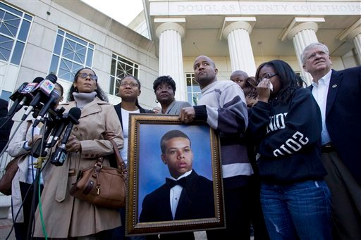 Monique Revaida, far left, mother of Bobby Tillman, 18, in the portrait being held, stands with loved ones in front of the Douglas County Courthouse after a hearing regarding the four men charged in her son's death.