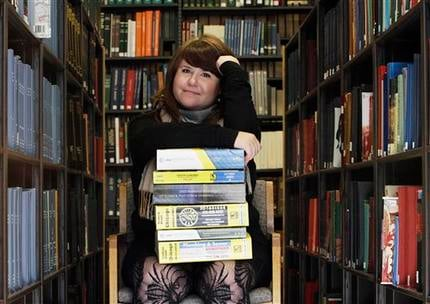 This photo taken Tuesday, Nov. 9, 2010, shows Emily Goodmann sitting with a small stack of phone books at the Northwestern University Library in Evanston, Ill. (AP Photo/Charles Rex Arbogast)