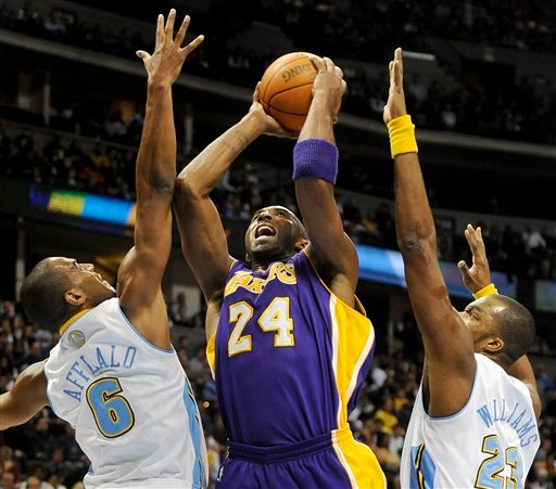Kobe Bryant, center, tries to put up a shot between Denver Nuggets guard Arron Afflalo, left, and forward Shelden Williams, right, in the first quarter of an NBA basketball game in Denver on Thursday, Nov. 11, 2010. (AP Photo/Chris Schneider)