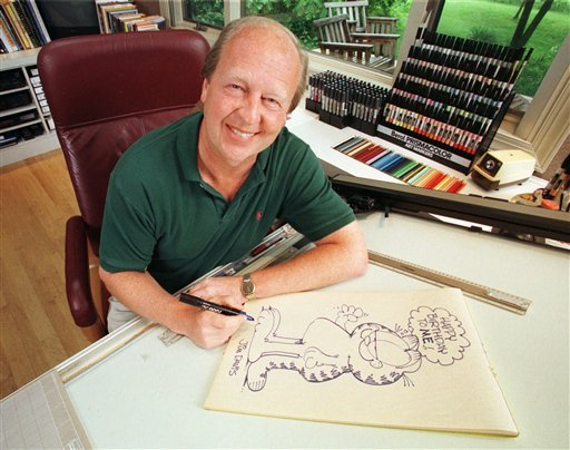 FILE - In this June 9, 1998 file photo, Garfield creator Jim Davis pauses after drawing the cartoon character in his Muncie, Ind., office. Davis apologized Thursday, Nov. 11, 2010, for a Garfield strip that some veterans may have found offensive.