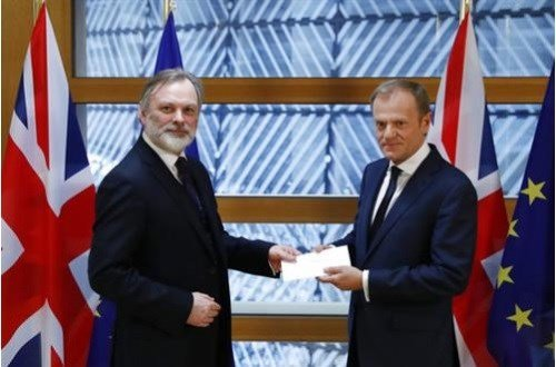 Britain's permanent representative to the European Union Tim Barrow, left, hand delivers British Prime Minister Theresa May's Brexit letter.