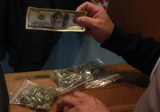 In this May 26, 2010, file photo, patient Andrew Vega buys bags of medical marijuana at the Coffeeshop Blue Sky dispensary in Oakland, Calif.  (AP Photo/Jeff Chiu, file)